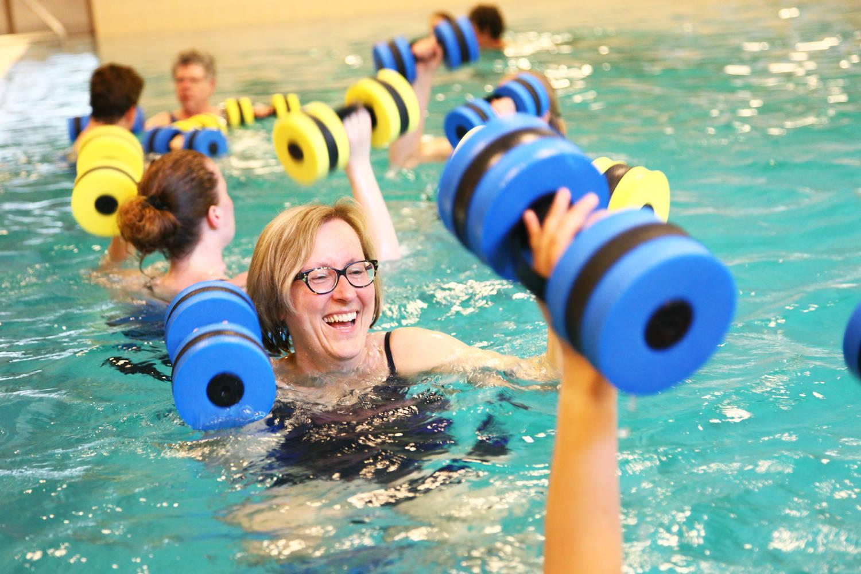 lachende vrouw in zwembad met gewichten in haar hand