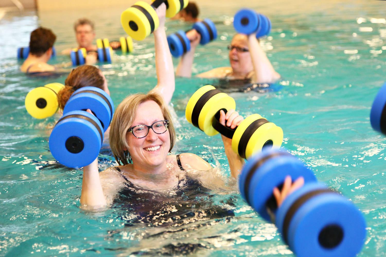 lachende vrouw met bril in het zwembad met blauw/gele gewichten in haar handen