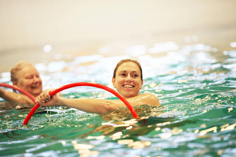 lachende vrouwen in zwembad met rode hoepels