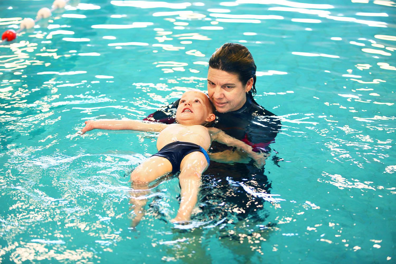 zwemleraar geeft individueel zwemles aan leerling