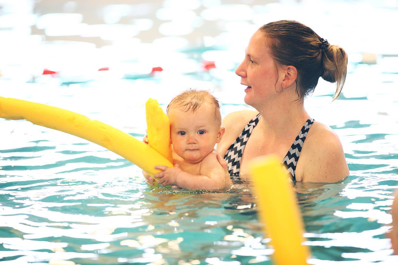lachende moeder met kind in het zwembad