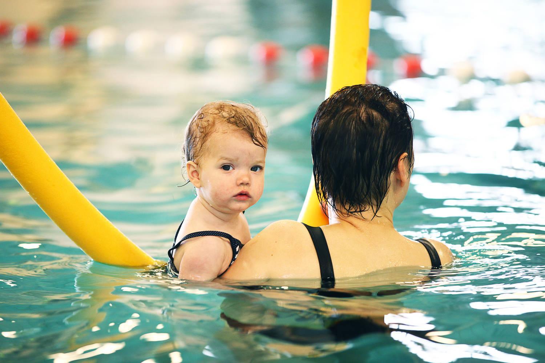 vrouw met kind in zwembad met gele zwemworst