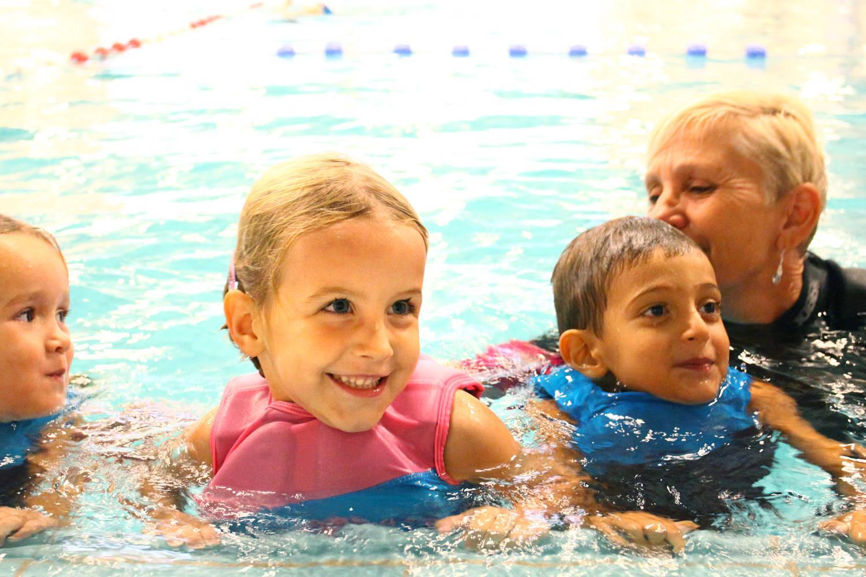 Lachende kinderen in zwembad met juffrouw