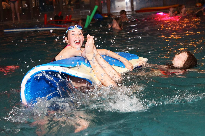 zwemfeest in zwembad, spelende kinderen op een blauwe drijfmat